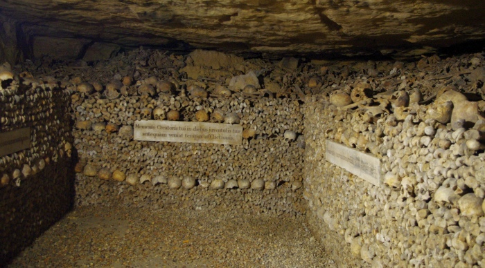 Image of the bone facades in the Paris Catacombs and piles of bones behind them.  Image credit: Ken and Nyetta on Flickr.