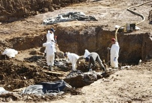 Photo of workers exhuming bodies from the Tomasica mass grave earlier this month