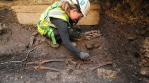 Photo via the BBC of an archaeologist excavating a body at the Lincoln Castle site.