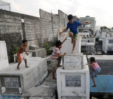 Photo via MailOnline of Children playing tag among stacked tombs