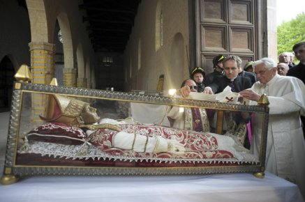 Pope Benedict XVI standing by the salvaged remains of Pope Celestine V, in 2009. The mask in this picture is the old wax one.  Photo from AP/L'Osservatore Romano via NPR.