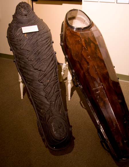"The ""Fisk Airtight Coffin of Cast or Raised Metal"" created by Almond D. Fisk.  Note the glass face plates and the shroud-like lid on the coffin on the left. Image Credit: Funeral Facts"