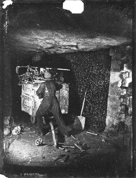Worker pushing a cart of bones in the Paris Catacombs, ca. 1861. Image from Wikipedia.