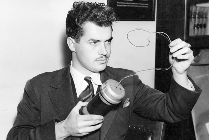 Photo of Jack Parsons from a 1938 edition of the LA Times. Parsons pictured w/the replica bomb he built for the Kynette trial. Image from Wikipedia.